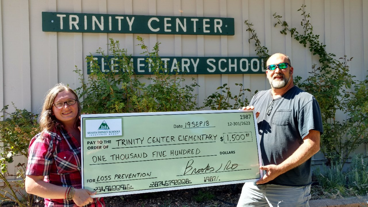 Employees of Trinity Center Elementary with large check